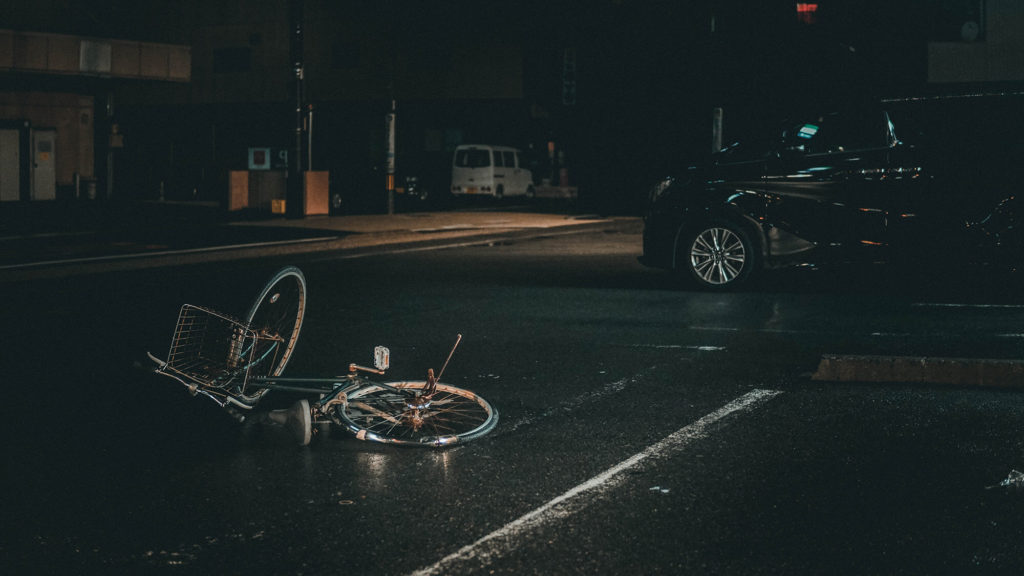 Bicycle knocked over on the road at night next to van