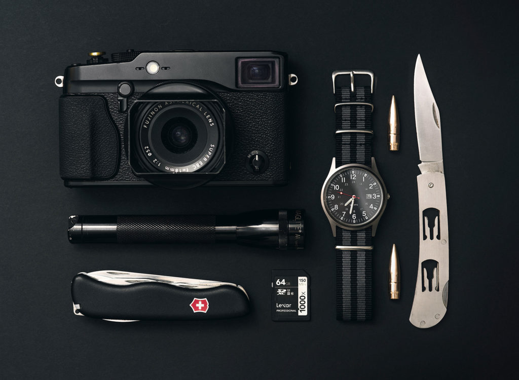 Camera, Swiss Army knife, watch and other other similar items lined up next to each other