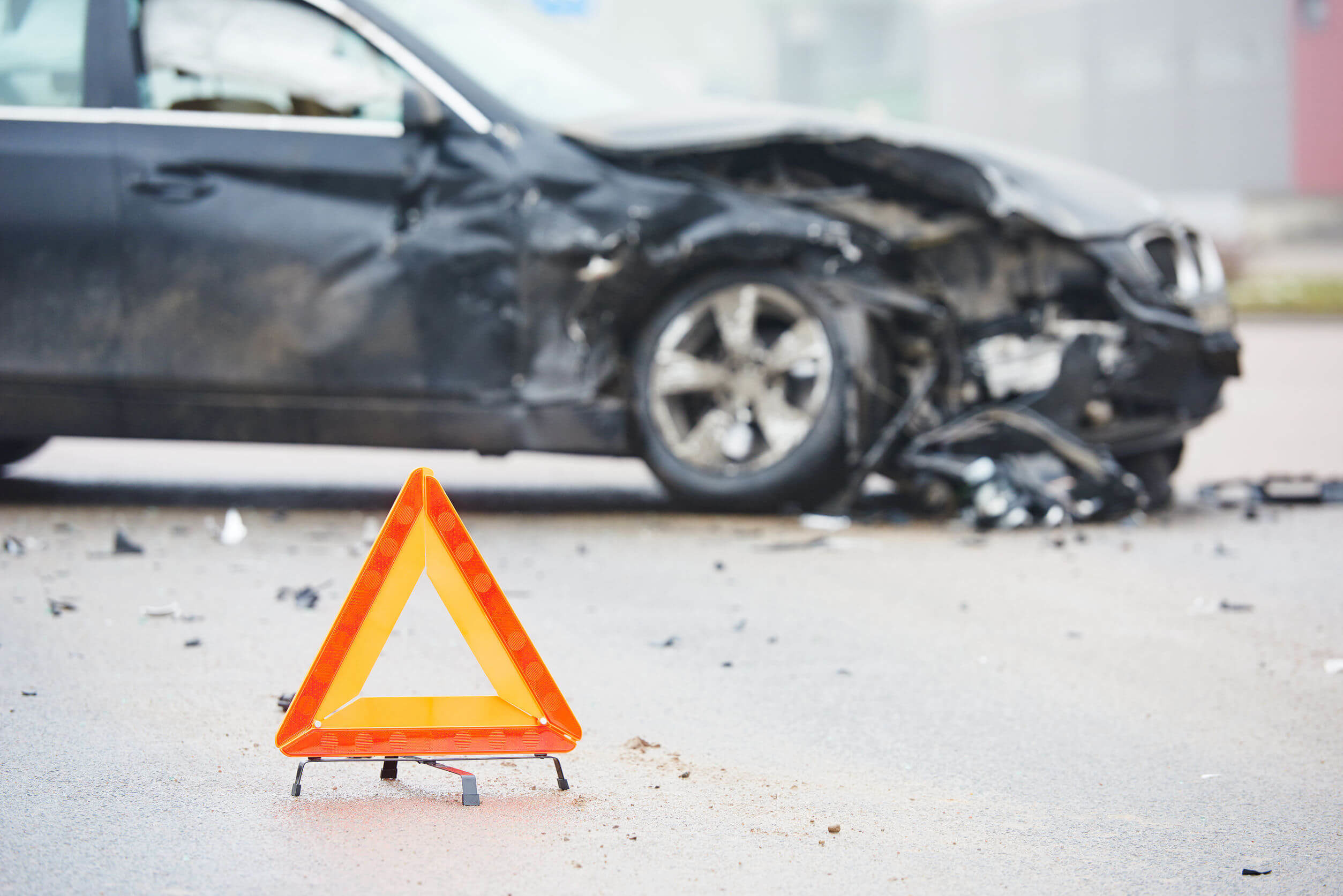 Crashed car in the background with a caution sign in the foreground