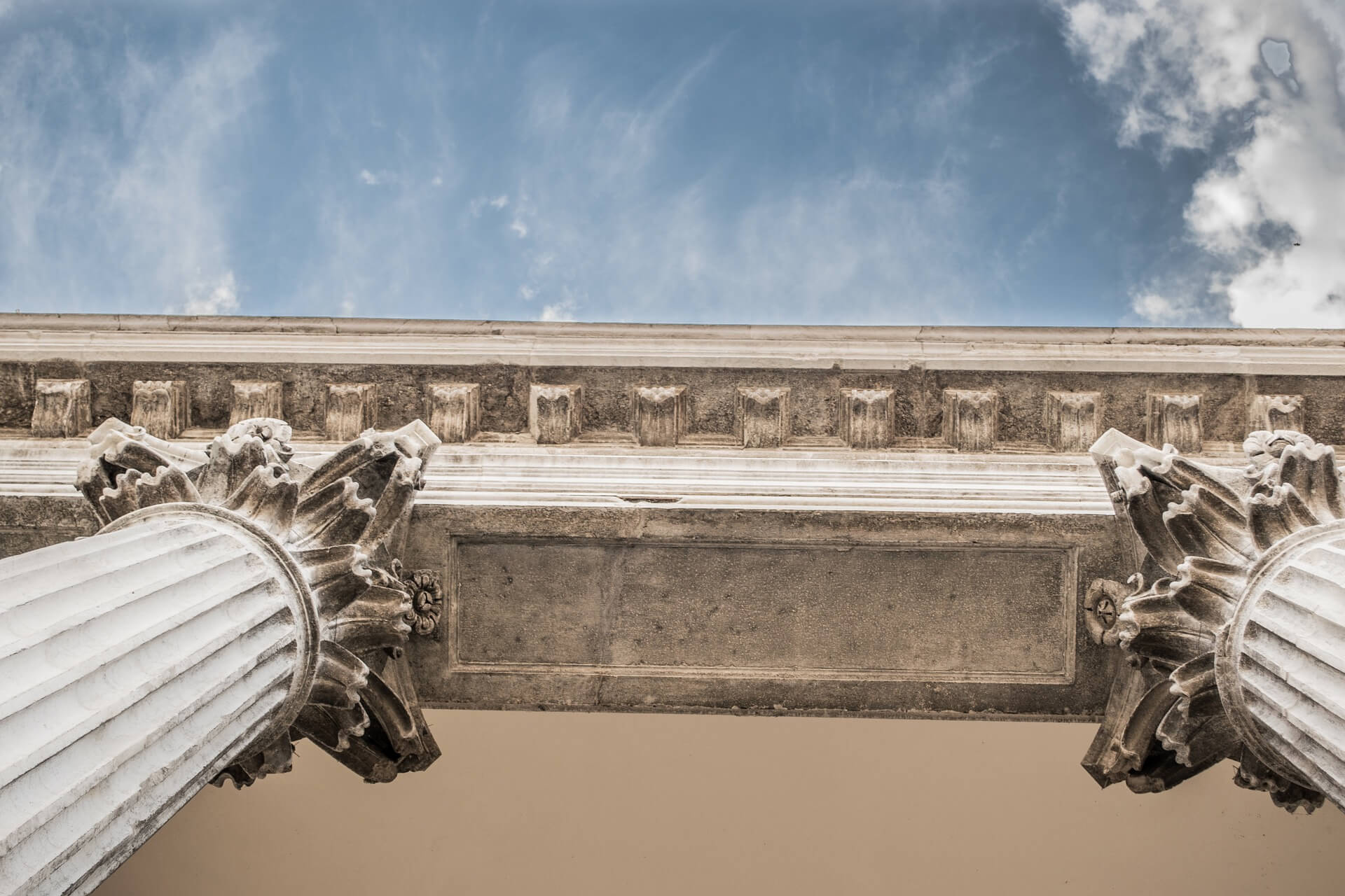 Worm's-eye view of a ionic-columned building with a partly cloudy sky in the background