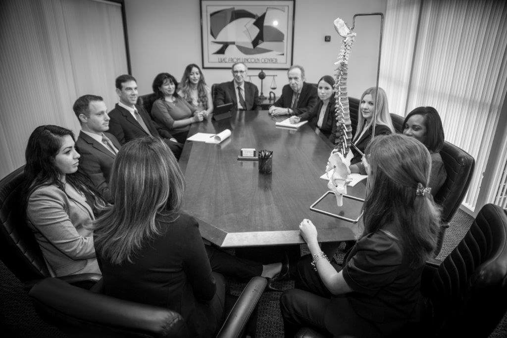 The Law Firm of Cohen & Cohen team sitting at boardroom table looking at a flexible spine model