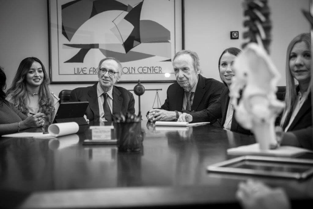 Members of the Cohen & Cohen team sitting around a boardroom table