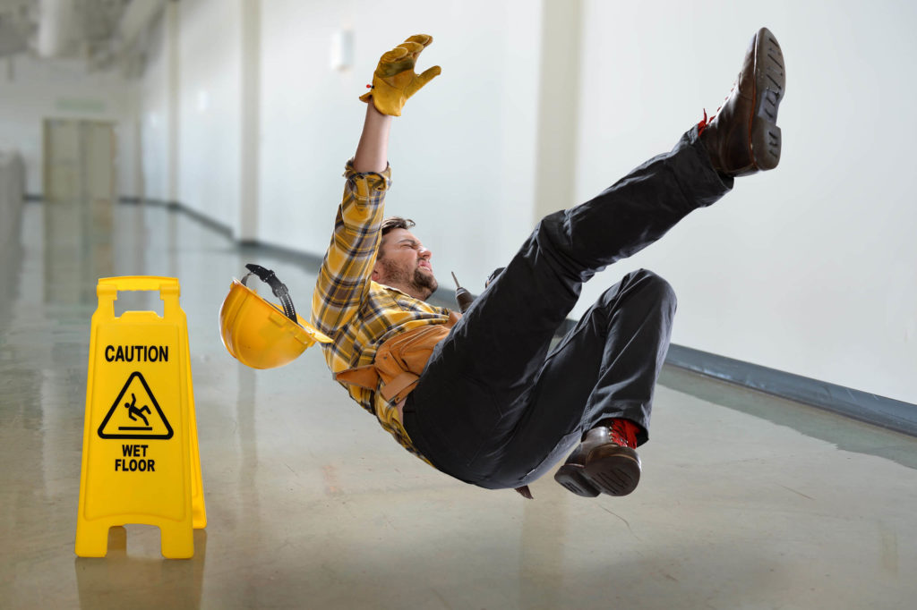 Construction Worker Slipping on Slick Floor Next to Caution Sign