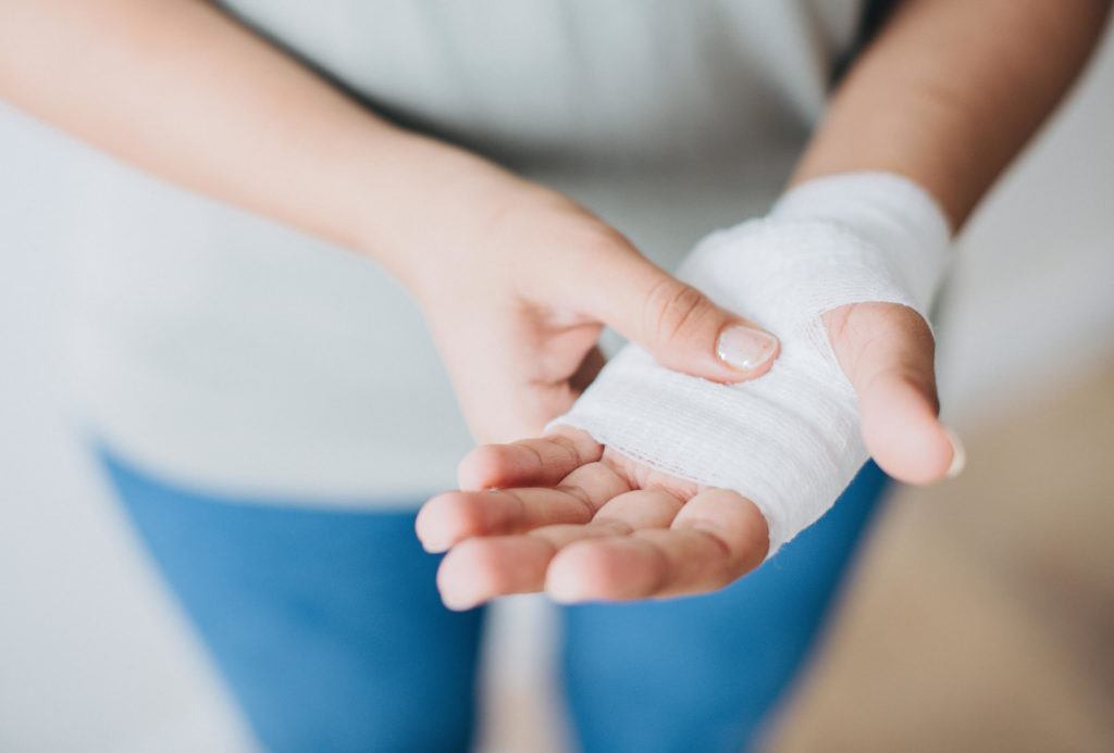 Woman holding her bandaged hand