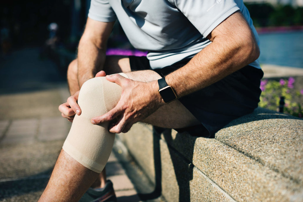 Man holding his knee wrapped in a bandage
