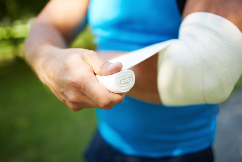 Athletic man wrapping elbow with bandage