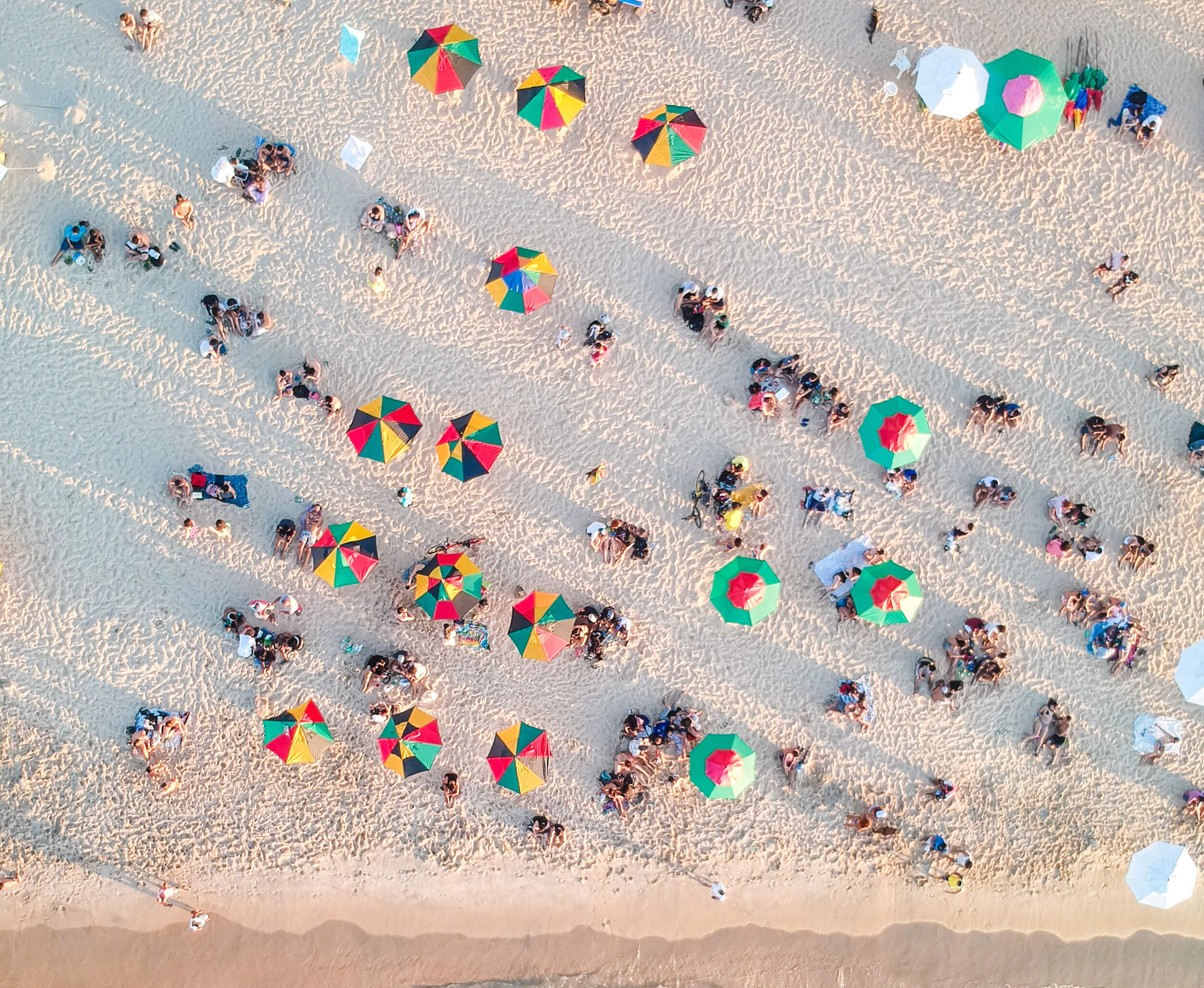 Aerial view of people sitting on sand on the beach