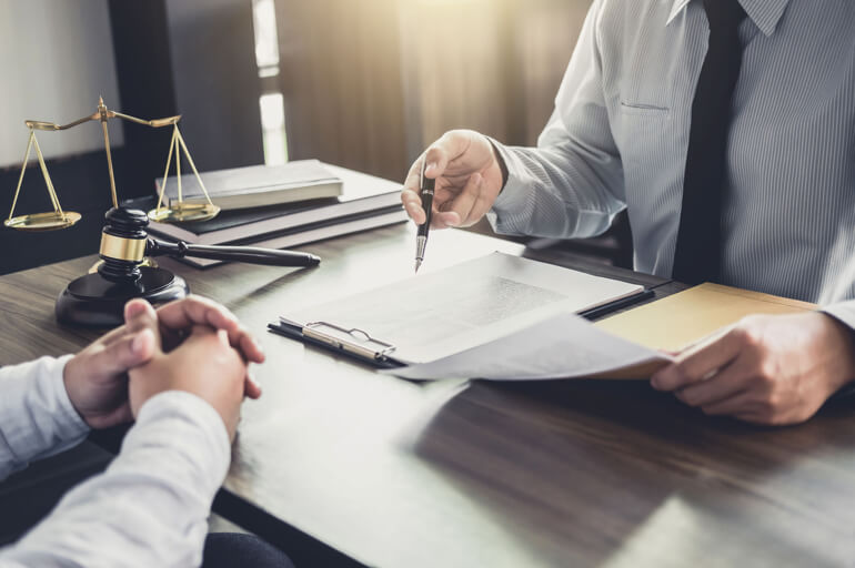 Lawyer Reviewing Paperwork with Client in an Office