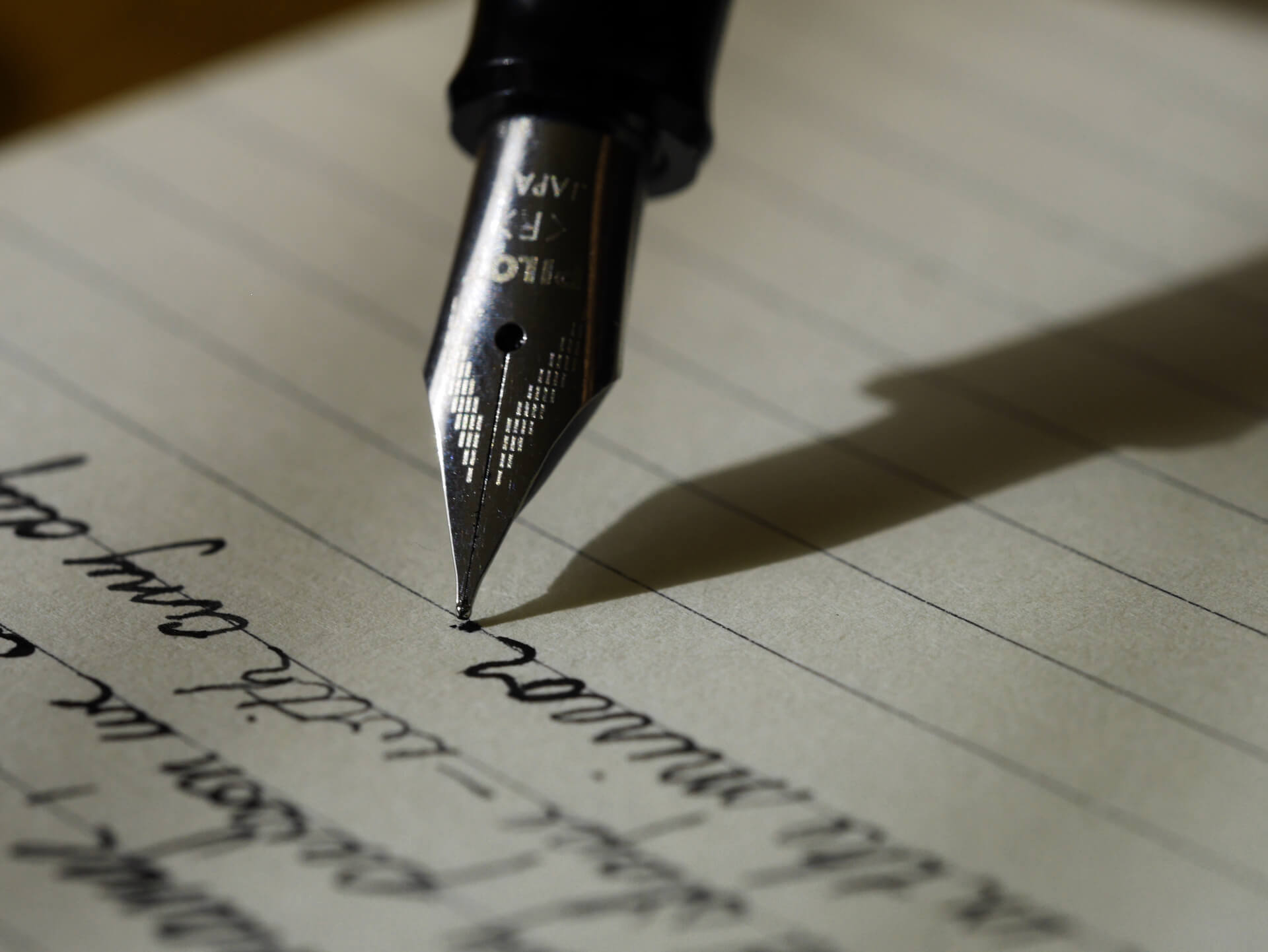 Fountain pen writing cursive in black ink on lined paper